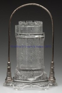 "FIGURAL KNOBBY CASTLE PICKLE CASTER, colorless,hexagonal base and original cover, glass and nickel-plated stand. Aetna Glass and Manufacturing Co. Fourth quarter 19th century. 10 1/4"" HOA, covered jar 7"" H, 4 3/8"" D base."