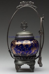 "Lot 562: VICTORIAN DECORATED PICKLE CASTER, cobalt bluewith full-round yellow enamel decoration, Benedict Co. quadruple-plate stand with tongs. Fourth quarter 19th century. 9 5/8"" HOA, jar 3"" H, 2"" D base."